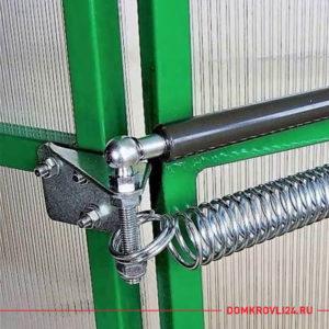 Черный термопривод на зеленой теплице